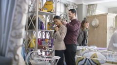 4K Couple shopping in fashion boutique, man helps girlfriend to fasten necklace - stock footage