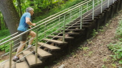 Adult man running jogging up the stairs outdoors in a forest nature on a forest Stock Footage