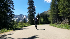 Young, sporty man jogging on road near mountains, super slow motion 240fps Stock Footage