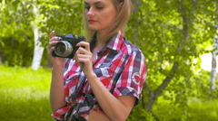 Beautiful young girl looking through a viewfinder in the camera. Slow motion - stock footage