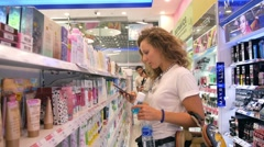 Woman Using Phone in Shopping Mall Choosing Cosmetics Stock Footage