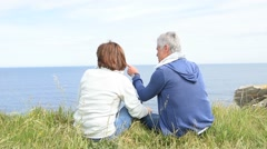Senior couple on rambling day sitting by cliff Stock Footage