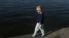 baby boy blond 8 years in a blue shirt, light trousers - stock footage