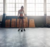 Tough fitness woman with kettle bell on floor - stock photo