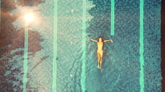 Young woman enjoying a pool at villa. Sun flares - stock footage