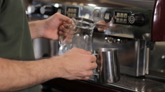 Barista pouring milk into a pitcher. Close up Stock Footage