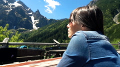 Woman sitting by table and admire amazing view of mountains Stock Footage