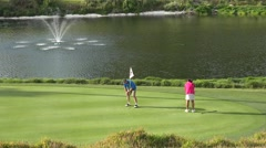 Golfers practice on the putting green of a golf course. Bermuda Stock Footage