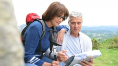 Senior couple of hikers reading orientation map - stock footage