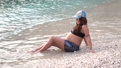 Pregnant lies down in cold sea water Stock Footage
