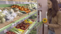 Beautiful girl chooses vegetables at the supermarket Stock Footage