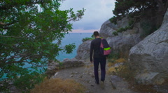 Young hipster with backpack suitable to the edge and looks at the stunning views Stock Footage