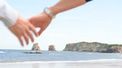 Senior couple holding hands at the beach - stock footage