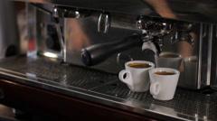 Barista picks up two cups of fresh made espresso. Medium shot Stock Footage