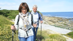 Senior couple walking on hiking track by the coast - stock footage