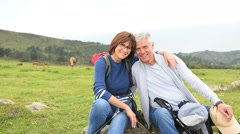Senior couple of hikers relaxing on rocks - stock footage