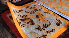 Woman demonstrates patterns of batik works at the factory in Kandy, Sri Lanka. - stock footage