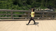 Young woman passing bridge in forest near river, super slow motion 240fps Stock Footage