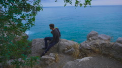 Young hipster guy sitting on the rock mountains near sea, man with a rucksack on Stock Footage