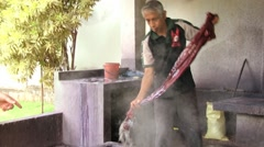 Man washes batik textile in hot water at the factory in Kandy, Sri Lanka. Stock Footage