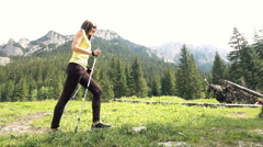 Young woman with poles walking on grass in forest, super slow motion 240fps Stock Footage