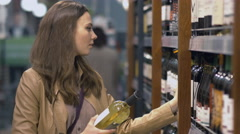Attractive woman chooses the wine bottle at the supermarket - stock footage