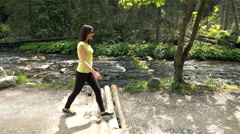 Young woman walking in forest by river, super slow motion 240fps Stock Footage