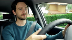 Handsome man with blue eyes driving car smiling 4K closeup - stock footage
