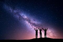 Landscape with Milky Way and silhouette of a happy family - stock photo