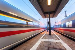 High speed passenger trains on railroad platform in motion Kuvituskuvat