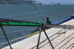 Fishing stand with angling rods on promenade Stock Photos