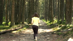 Young, sporty woman jogging in forest, super slow motion 240fps Stock Footage