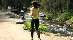 Young, sporty woman jogging near river in forest, super slow motion 240fps Stock Footage