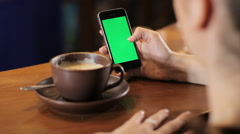 Woman works in smartphone with green screen and drink coffee. Shot from behind Stock Footage