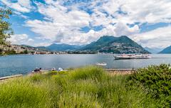 View of Lake Lugano with ferry that arrives - stock photo