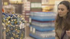 Nice girl chooses sweets at the supermarket Stock Footage
