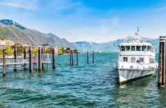 Ferry boat at the pier on the shore of lake Maggiore. Stock Photos