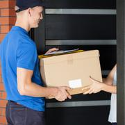 Delivery man giving parcel to homeowner Stock Photos