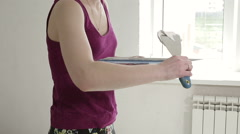 Builder female indoor worker plastering wall with spatula trowel tool Stock Footage
