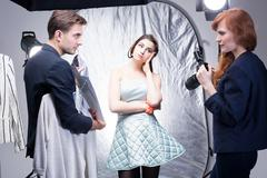 Female fashion photographer in a photo studio with a designer and his model, ana Stock Photos