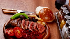 Fresh roast bbq beef meat ribeye steak on wooden plate served with tomato juice Stock Footage