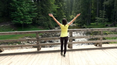 Young woman stretching leg on bridge by river in forest, super slow motion 240fp Stock Footage