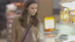 Lovely girl buyer chooses frozen beef in the freezer - stock footage
