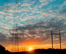 Silhouettes high voltage electric pylon in sunset background Stock Photos