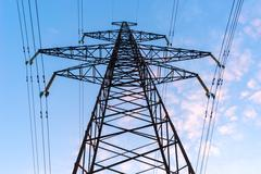 Silhouettes high voltage electric pylon in sunset background - stock photo