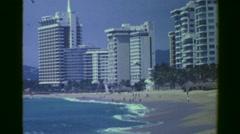 1978: High rise resort hotels facing popular tourism crashing wave beach.  Stock Footage