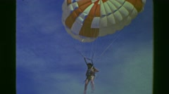 1978: Parasailing woman calming landing on beach caught by staff. ACAPULCO, - stock footage