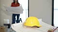 View of helmet and blueprints at new home, woman reading documents in the backgr Stock Footage