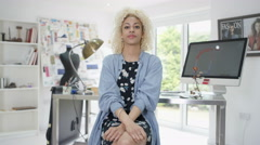 4K Portrait smiling designer sitting at her desk in studio. Stock Footage