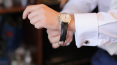 The man in the white shirt fixing watches. Close-up hands on interior background Stock Footage